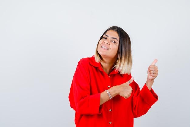 Mooie vrouw die opzij wijst met duimen in rode blouse en er vrolijk uitziet. vooraanzicht.