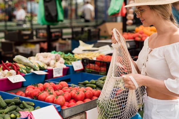 Mooie vrouw die organische zak voor groenten gebruikt
