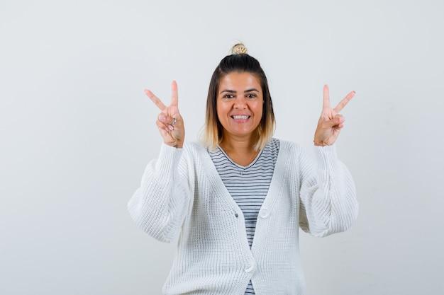 Mooie vrouw die overwinningsgebaar in t-shirt, vest toont en er vrolijk uitziet.