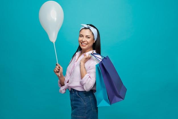 Mooie vrouw die papieren zakken en ballon en poseren