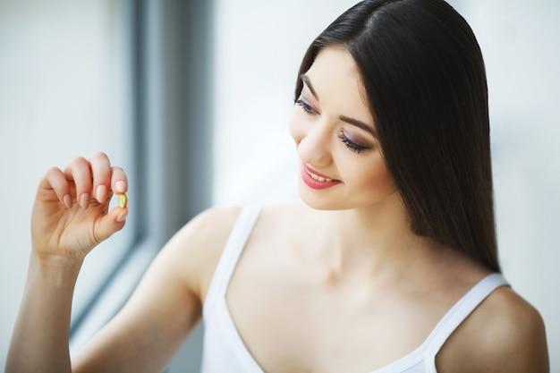 Mooie vrouw die pil, geneeskunde neemt. vitaminen en supplementen