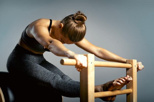 Mooie vrouw die pilatesoefening doet, die op vaten traint