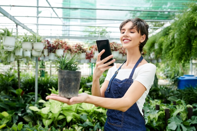 Mooie vrouw die plant fotografeert