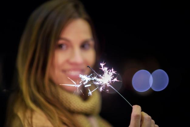 Mooie vrouw die pret, met sterretje in haar handen heeft die nieuwe jaarvooravond vieren