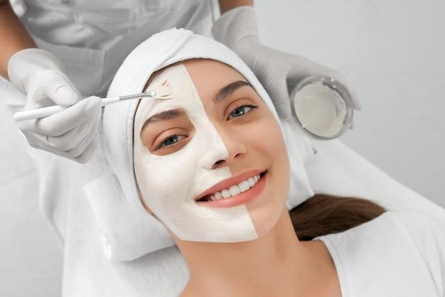 Mooie vrouw die procedure voor gezicht in schoonheidsspecialiste doet