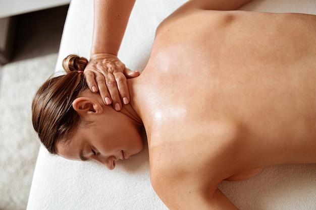 Mooie vrouw die professionele massage ontvangt in spa salon