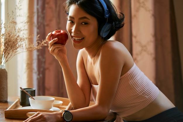 Mooie vrouw die rode appel eet