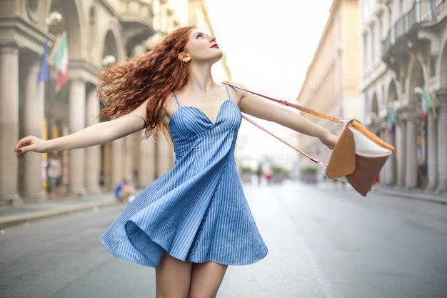 Mooie vrouw die rond de straat slingert, die een leuke lichtblauwe jurk draagt