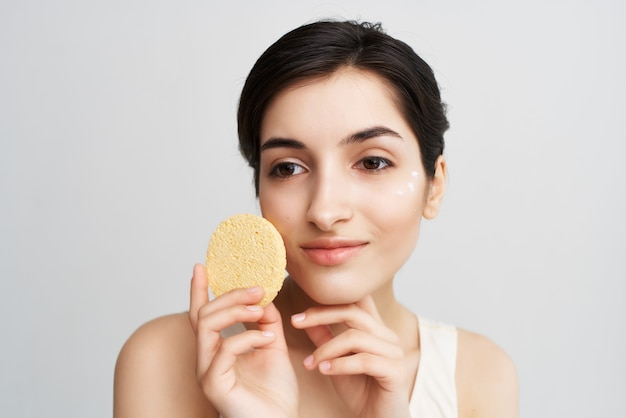 Mooie vrouw die room met een spons op haar gezichtsclose-up aanbrengt