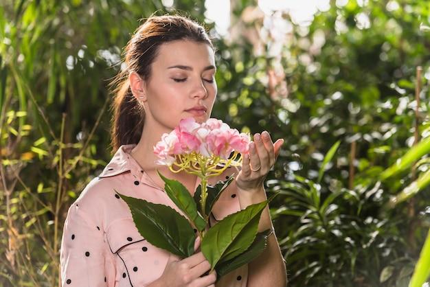 Mooie vrouw die roze bloem ruikt