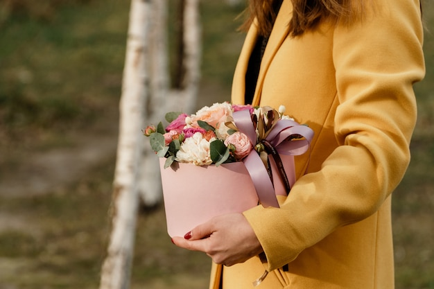 Mooie vrouw die roze doos met bloemen houdt. gift to women's day.