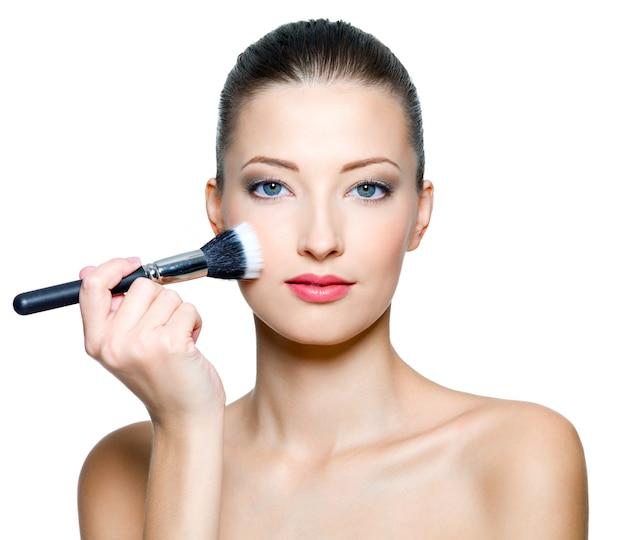Mooie vrouw die samenstelling op gezicht met kosmetische borstel doet die op wit wordt geïsoleerd