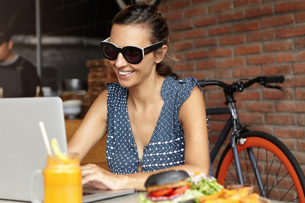 Mooie vrouw die schaduwen dragen die voor open laptop zitten, die videogesprek voeren