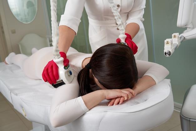 Mooie vrouw die schoonheidstherapie krijgt tegen cellulitis met lpg-machine. lpg-massage voor het heffen van lichaam