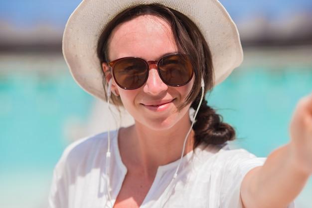 Mooie vrouw die selfie achtergrond het overzees neemt