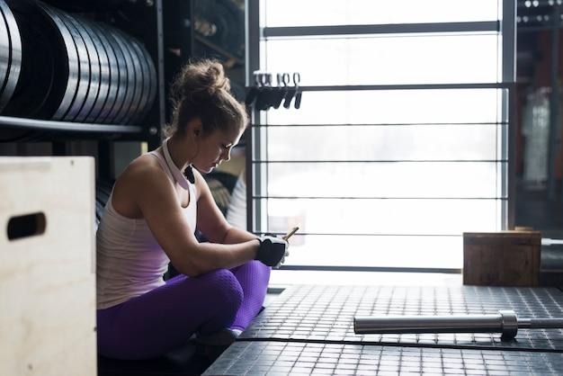 Mooie vrouw die smartphone in gymnastiek gebruikt