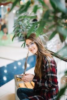 Mooie vrouw die smartphone op bank in winkelcomplex gebruiken