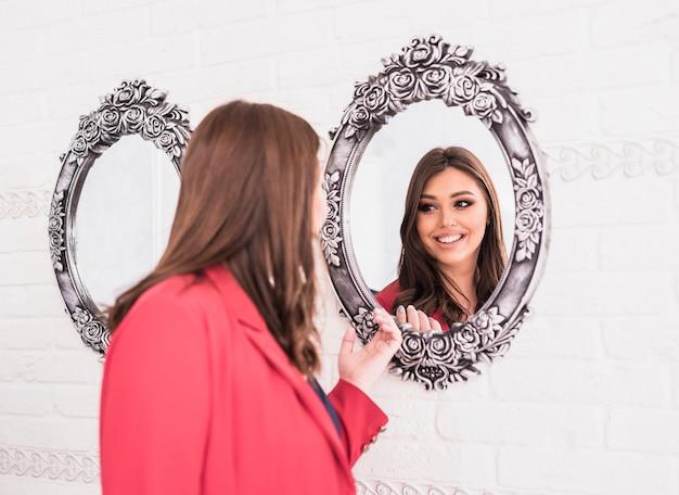 Mooie vrouw die spiegel bekijkt