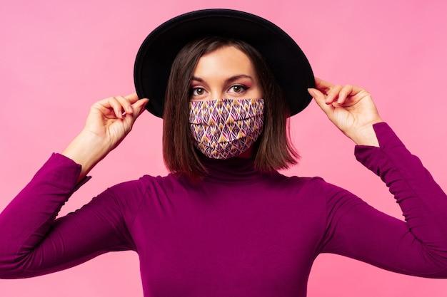 Mooie vrouw die stijlvol beschermend gezichtsmasker draagt. zwarte hoed