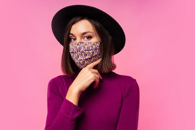 Mooie vrouw die stijlvol beschermend gezichtsmasker draagt. zwarte hoed Gratis Foto