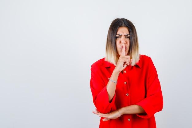 Mooie vrouw die stiltegebaar in rode blouse toont en ernstig, vooraanzicht kijkt.