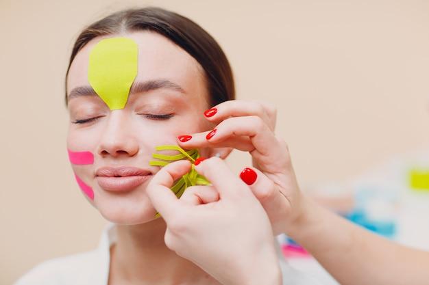 Mooie vrouw die tape opheffende behandeling op het gezicht toepast