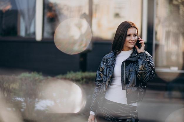 Mooie vrouw die telefoon in openlucht in park met behulp van
