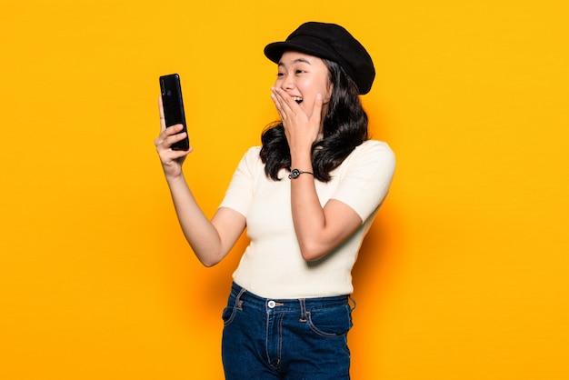 Mooie vrouw die terwijl video die gele achtergrond uitnodigen glimlachen