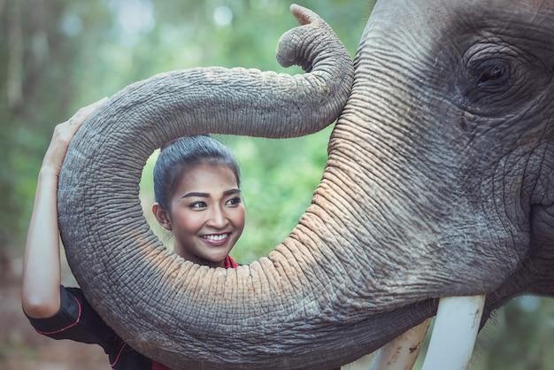 Mooie vrouw die thaise zijde traditionele kleding met olifant, surin provincie, thailand draagt