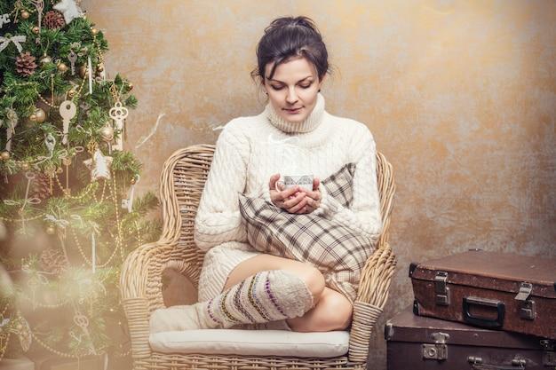 Mooie vrouw die thee of koffie drinkt zittend in een stoel met kussens in het kerstinterieur