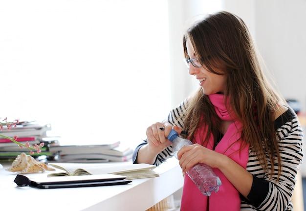 Mooie vrouw die thuis bestudeert