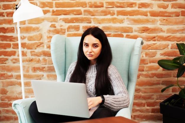 Mooie vrouw die thuis blijft en online aan laptop werkt