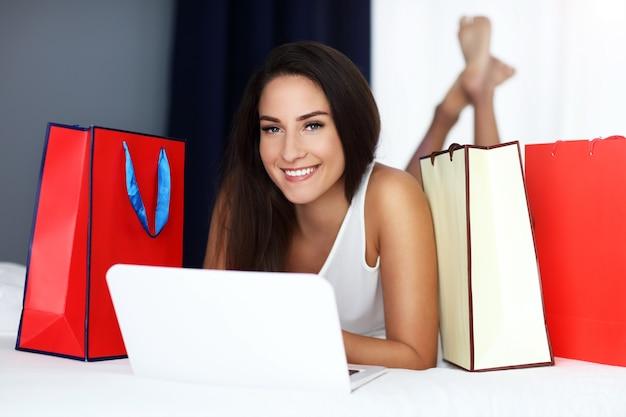 Mooie vrouw die thuis online winkelt
