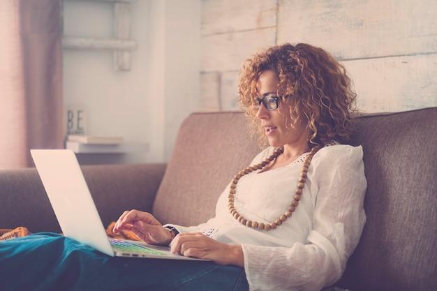 Mooie vrouw die thuis op de bank ligt en werkt of een film kijkt met haar laptop - dame met verbaasde uitdrukking die iets online wint - gok en speel met internetspellen
