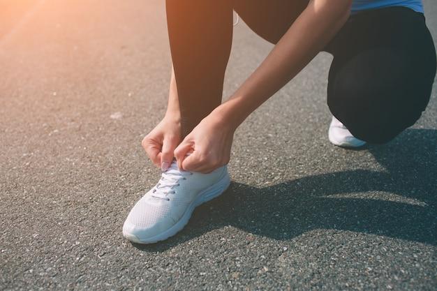 Mooie vrouw die tijdens zonsondergang loopt. jong geschiktheidsmodel dichtbij kust. gekleed in sportkleding. snoeren sneakers