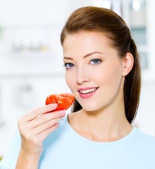 Mooie vrouw die tomaat in keuken eet