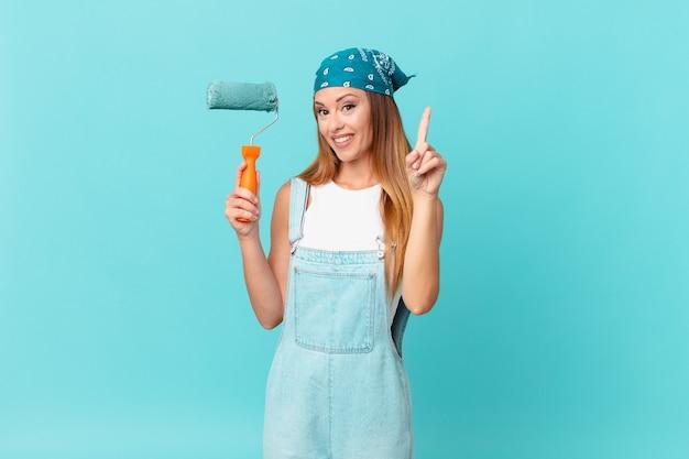 Mooie vrouw die trots en zelfverzekerd glimlacht en nummer één maakt door een nieuwe huismuur te schilderen