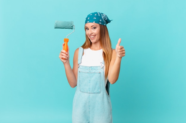 Mooie vrouw die trots is, positief glimlacht met duimen omhoog die een nieuwe huismuur schildert