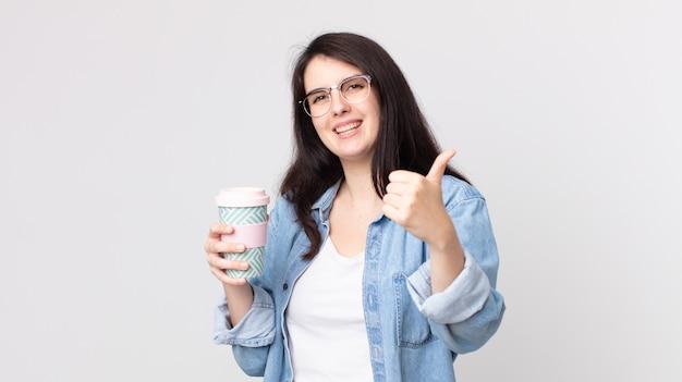 Mooie vrouw die trots is, positief glimlacht met duimen omhoog en een afhaalkoffie vasthoudt