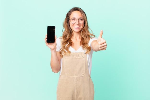 Mooie vrouw die trots is, positief glimlacht met duimen omhoog en een smartphone vasthoudt