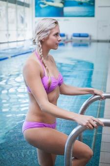 Mooie vrouw die uit het water bij het zwembad