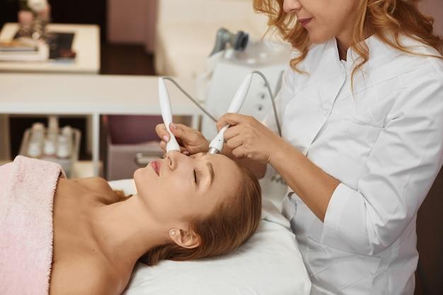 Mooie vrouw die ultrasone gezichtsscrubbing en massage ontvangt. cosmetologie en gezichtshuidverzorging. gezichtsbehandeling, gezichtsreiniging. elektronische stimulatie.