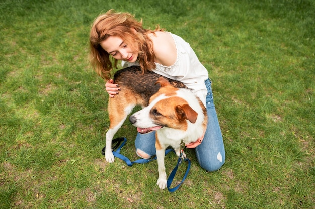 Mooie vrouw die van aard met haar hond geniet