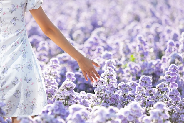 Mooie vrouw die van bloemengebied geniet