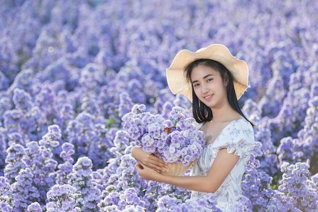 Mooie vrouw die van bloemengebied geniet Gratis Foto