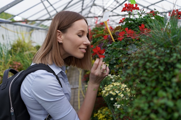 Mooie vrouw die van de bloemenschoonheid en het aroma in de serre geniet.