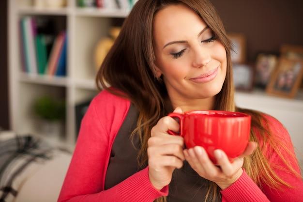 Mooie vrouw die van de geur van verse koffie geniet