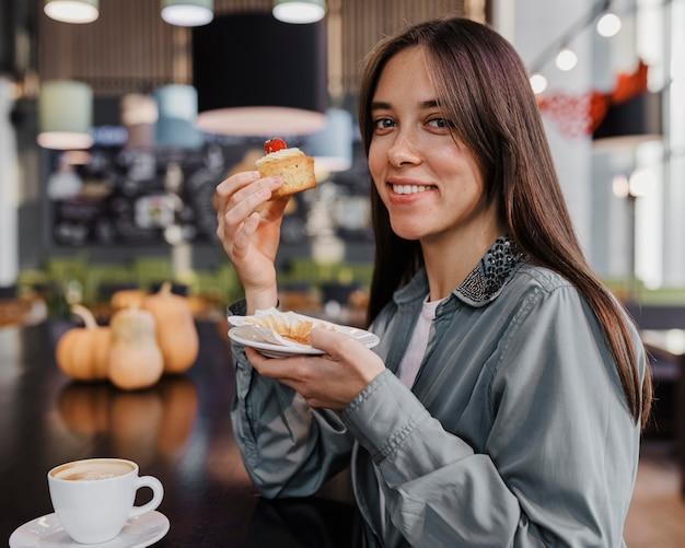 Mooie vrouw die van een koffie en een cake geniet