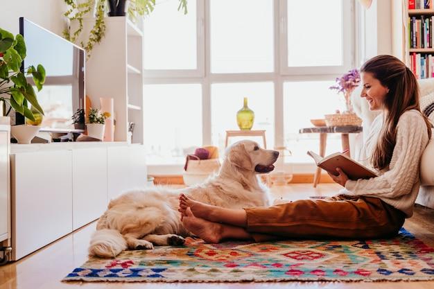 Mooie vrouw die van een kop van koffie thuis geniet tijdens gezond ontbijt. schrijven op laptop. schattige golden retrieverhond bovendien. lifestyle binnenshuis