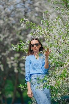 Mooie vrouw die van geur geniet in de lentekersentuin